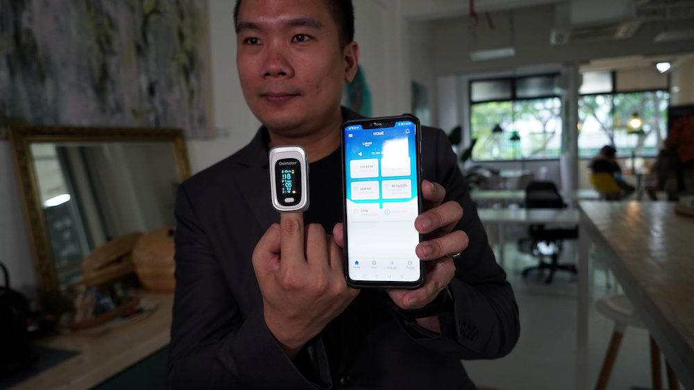 Nervotec founder Jonathan Lau shows the comparison in vital signs readings between his company's app and a pulse oxygen monitor, in Singapore February 19, 2021. — Reuters pic
