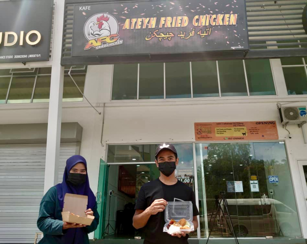 Kafe Ateyh Fried Chicken outlet owners Siti Nazirah Norzri (left) and her husband Mohammad Atif Wan Kamal started their initiative to provide free food for the needy during the second phase of the movement control order (MCO). — Picture by Ben Tan