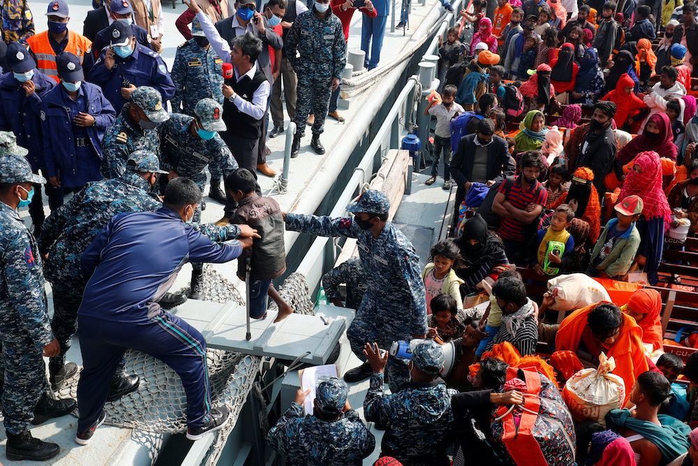 Bangladesh Navy personnel help a disabled Rohingya refugee child to get off from a navy vessel as they arrive at the Bhasan Char island in Noakhali district, Bangladesh, December 29, 2020. — Reuters pic