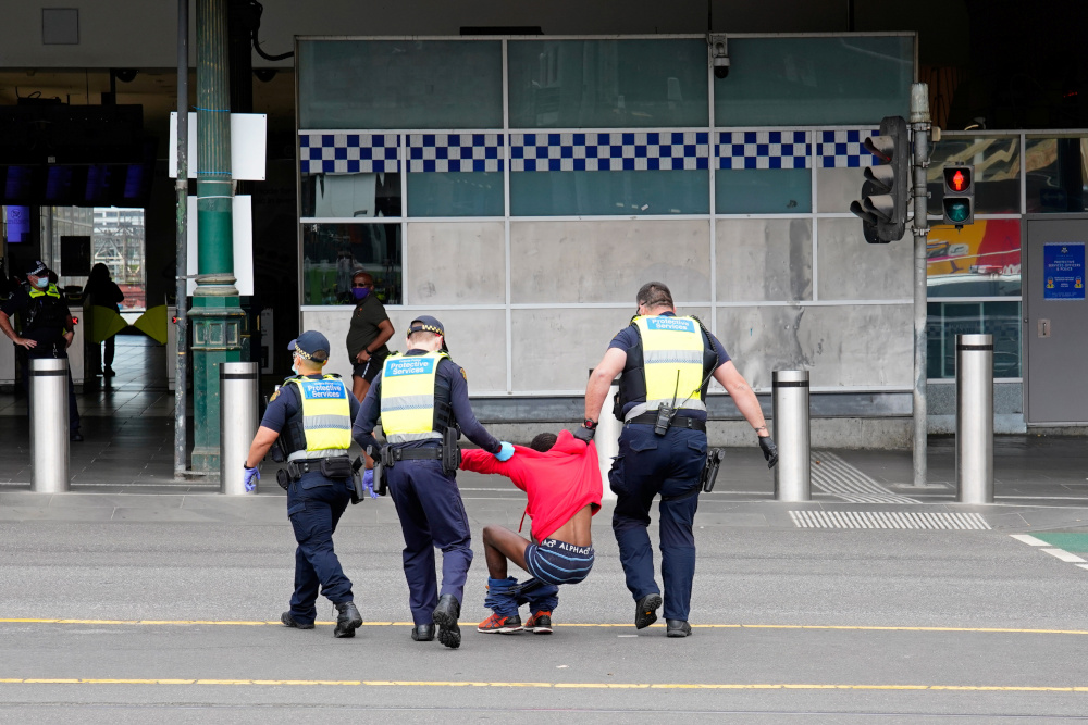 Victoria Police Protective Services Officers apprehend a man on the first day of a five-day lockdown implemented in the state of Victoria in Melbourne Australia