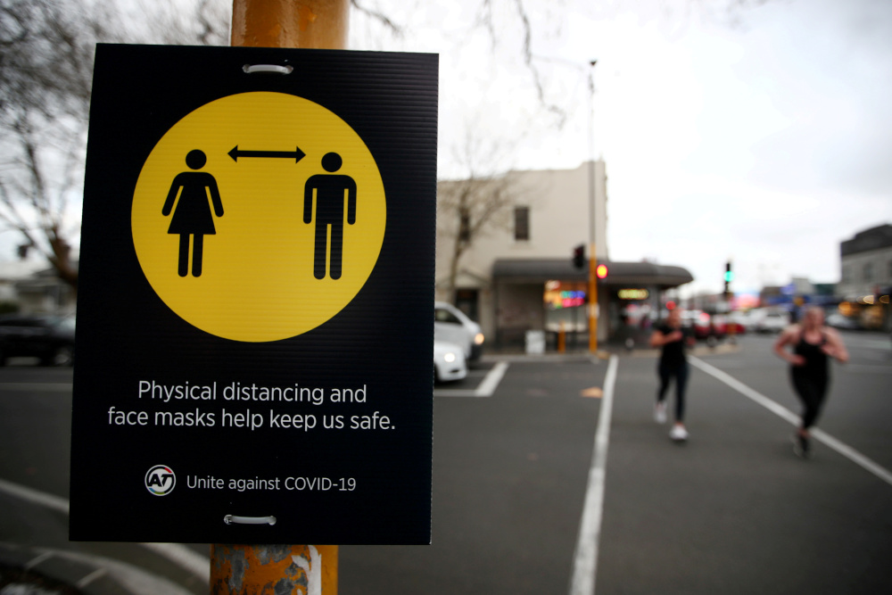 People jog past a social distancing sign on the first day of New Zealand's new coronavirus disease safety measure that mandates wearing of a mask on public transport, in Auckland, August 31, 2020. — Reuters pic