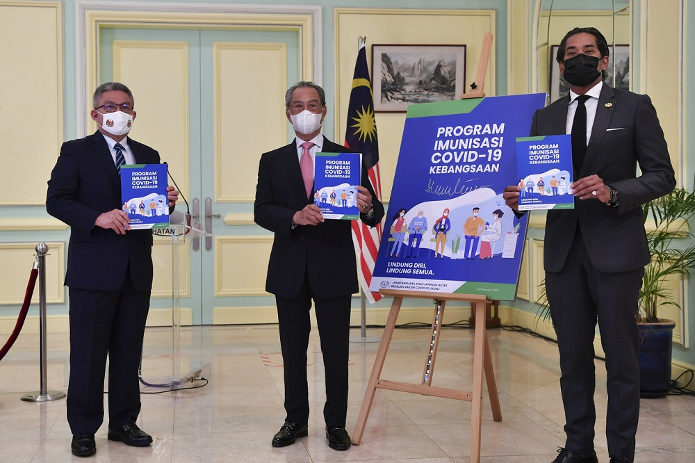 (From left) Health Minister Datuk Seri Dr Adham Baba, Prime Minister Tan Sri Muhyiddin Yassin and Minister of Science, Technology and Innovation Khairy Jamaluddin at the launch of the National Covid-19 Immunisation Programme Handbook at the Perdana Putra Building in Putrajaya February 16, 2021. — Bernama pic