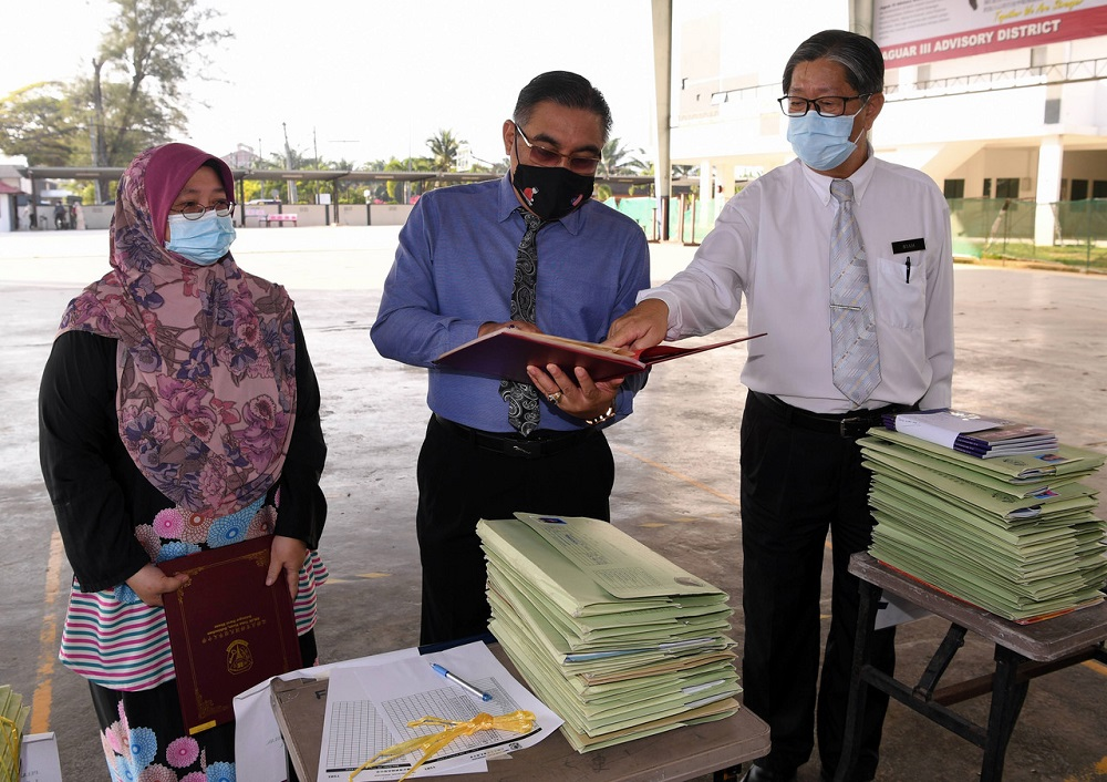 Deputy Education Minister 1 Muslimin Yahaya (centre) during a visit to Sekolah Menengah Jenis Kebangsaan Yoke Kuan on the first day of the Sijil Pelajaran Malaysia (SPM) examination in Sekinchan February 22, 2021. — Bernama pic