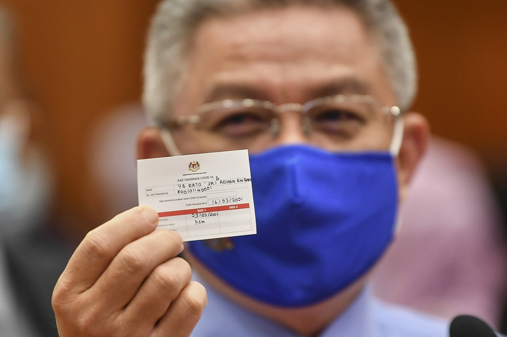 Health Minister Datuk Seri Dr Adham Baba with a sample of the vaccination card during a simulation exercise for the National Covid-19 Immunisation Programme, in Putrajaya February 23, 2021. ¬— Bernama pic