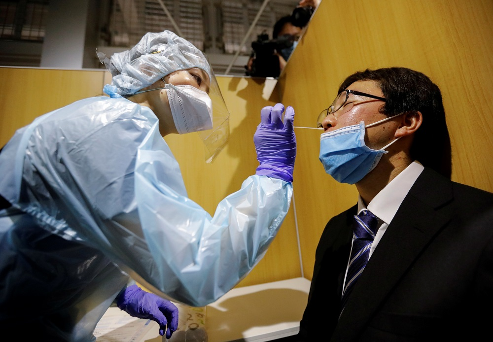 File picture shows a medical worker conducting a simulation for a polymerase chain reaction (PCR) test at the newly opened Narita International Airport PCR Center in Narita, east of Tokyo, Japan November 2, 2020. ― Reuters pic