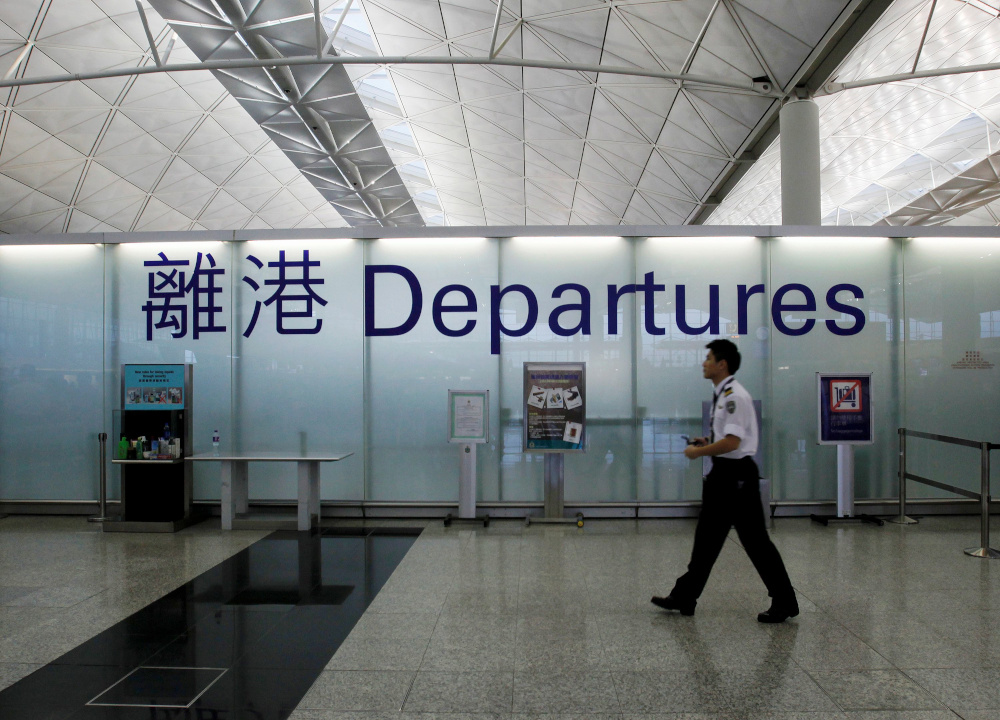 An airport security guard walks past a sign at the departure hall of Hong Kong Airport June 23, 2013. — Reuters pic