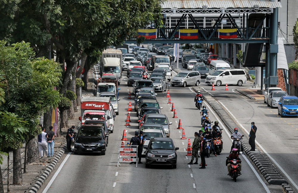 Police personnel conduct a roadblock at Jalan Loke Yew during MCO 2.0, February 19, 2021. — Picture by Ahmad Zamzahuri