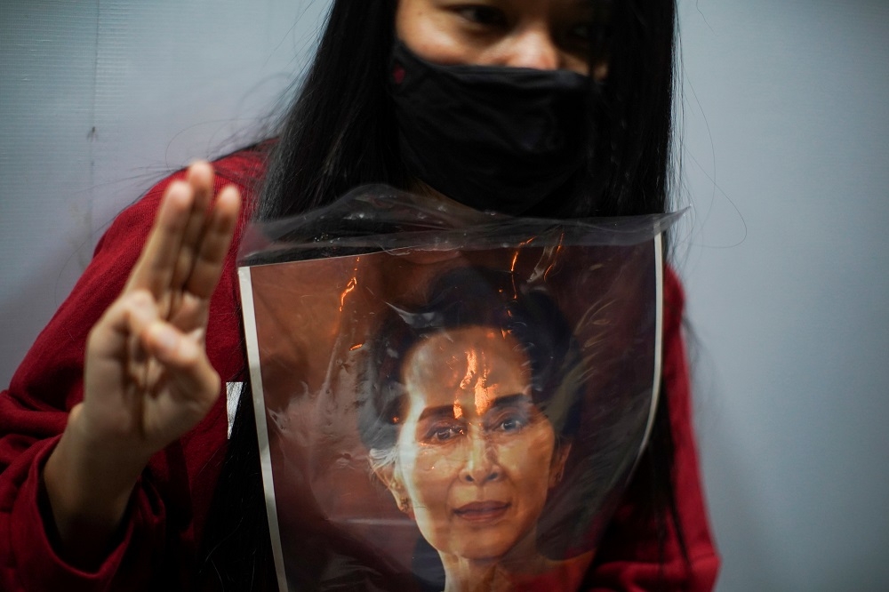 A demonstrator flashes a three-finger salute while holding a picture of Aung San Suu Kyi as Myanmar citizens living in Thailand protest against the military coup, outside Myanmar embassy in Bangkok, February 4, 2021. ― Reuters pic