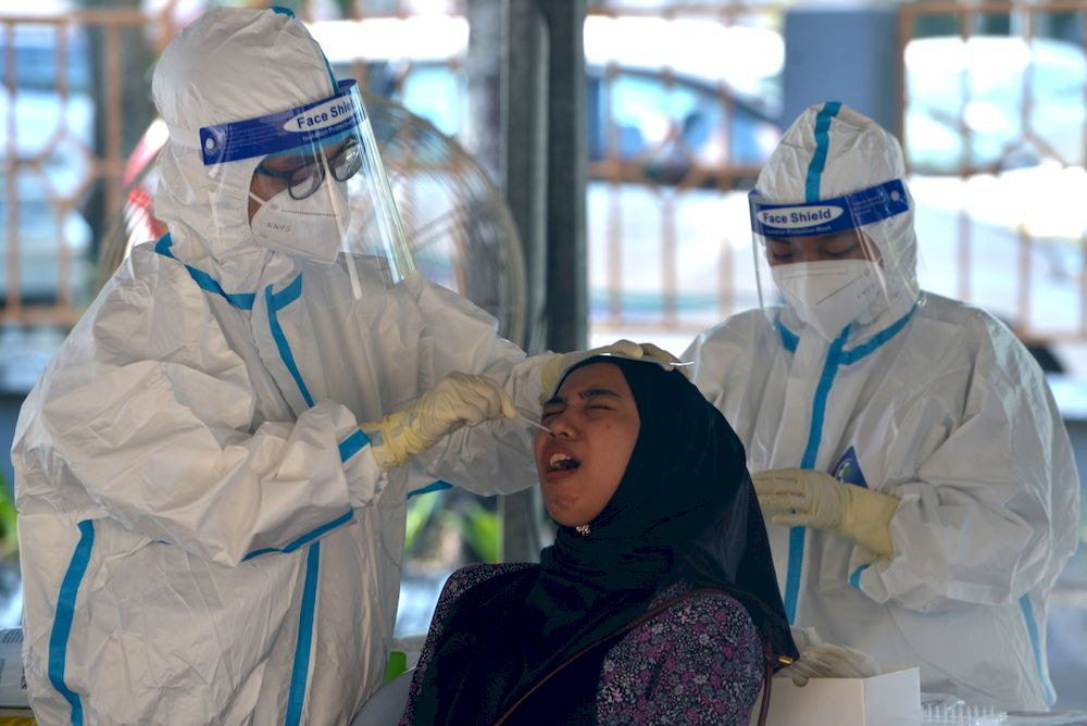 A health worker administering Covid-19 test on a resident in Puchong, February 28,2021. — Picture by Miera Zulyana