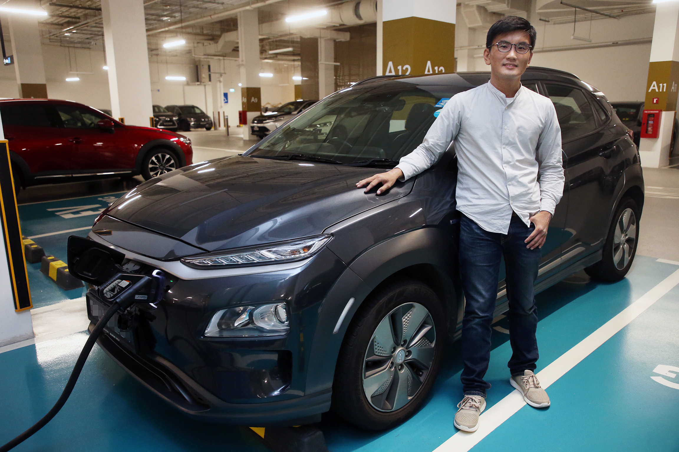 Mr Koh Jie Meng, who has been driving an electric vehicle (EV) since 2019, said he now has no doubts about the feasibility of owning one, even as a HDB dweller. — Photo by Ooi Boon Keong for TODAY