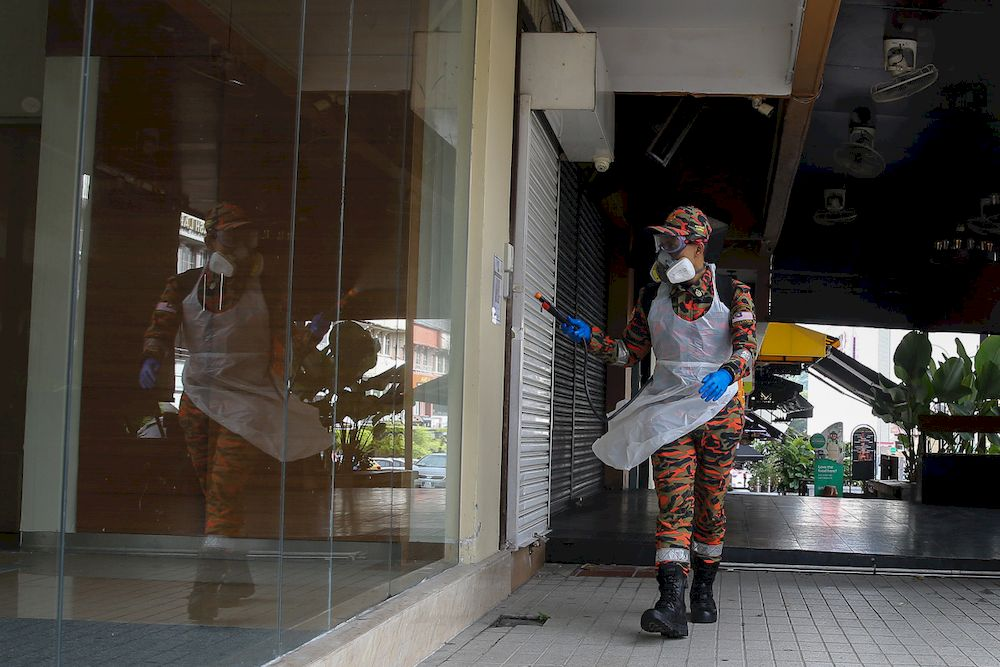 A firefighter spraying disinfectant at a business area during Movement Control Order phase at Bangsar in Kuala Lumpur January 23, 2021. — Picture by Yusof Mat Isa