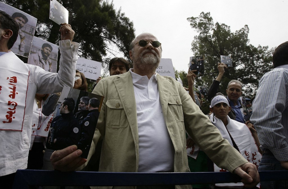 A file photo taken on April 30, 2010, shows Anis Naccache holding a picture of Georges Ibrahim Abdallah during a demonstration outside the French embassy in the capital Beirut. — AFP pic