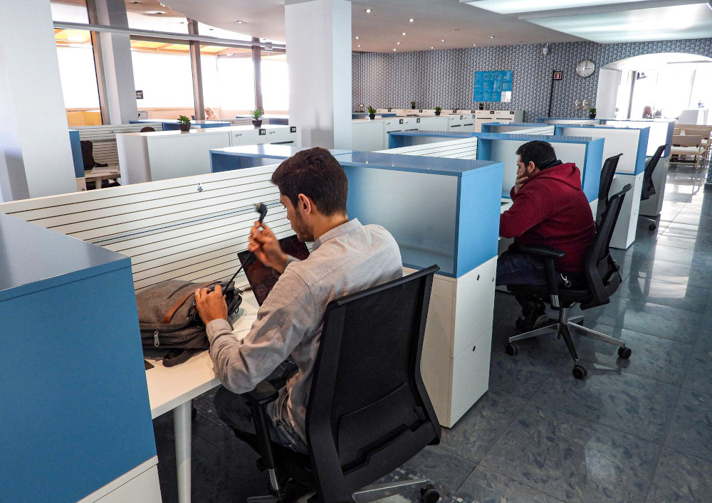 People sit in half-cubicles as they work at the Nuqta coworking space, which provides workstations, meeting rooms, and a cafeteria for small businesses and entrepreneurs in Tripoli. — AFP pic