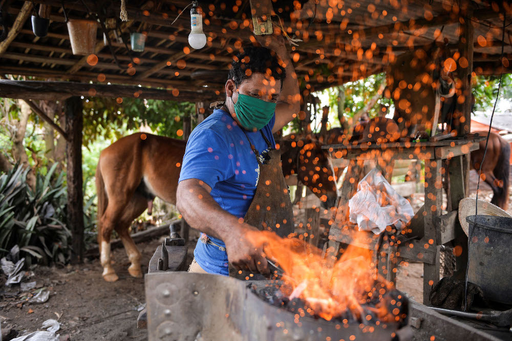 Yusmani Garcia, a blacksmith and tour guide, makes a horseshoe at his house in Vinales, Cuba. — AFP pic
