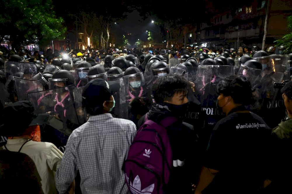 Pro-democracy protesters face off with riot police during a rally demanding the end of Thailand's royal defamation law in Bangkok on February 10, 2021. — AFP pic