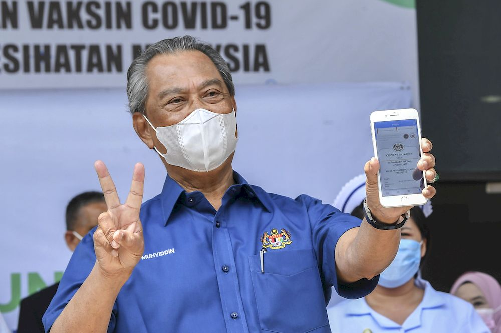 Prime Minister Tan Sri Muhyiddin Yassin looked cheerful while showing the Covid-19 vaccination status displayed on MySejahtera application after receiving the Pfizer-BioNTech Covid-19 vaccine injection at the District Health Centre in Precinct 11, Putrajaya, Feb 24, 2021. — Bernama pic