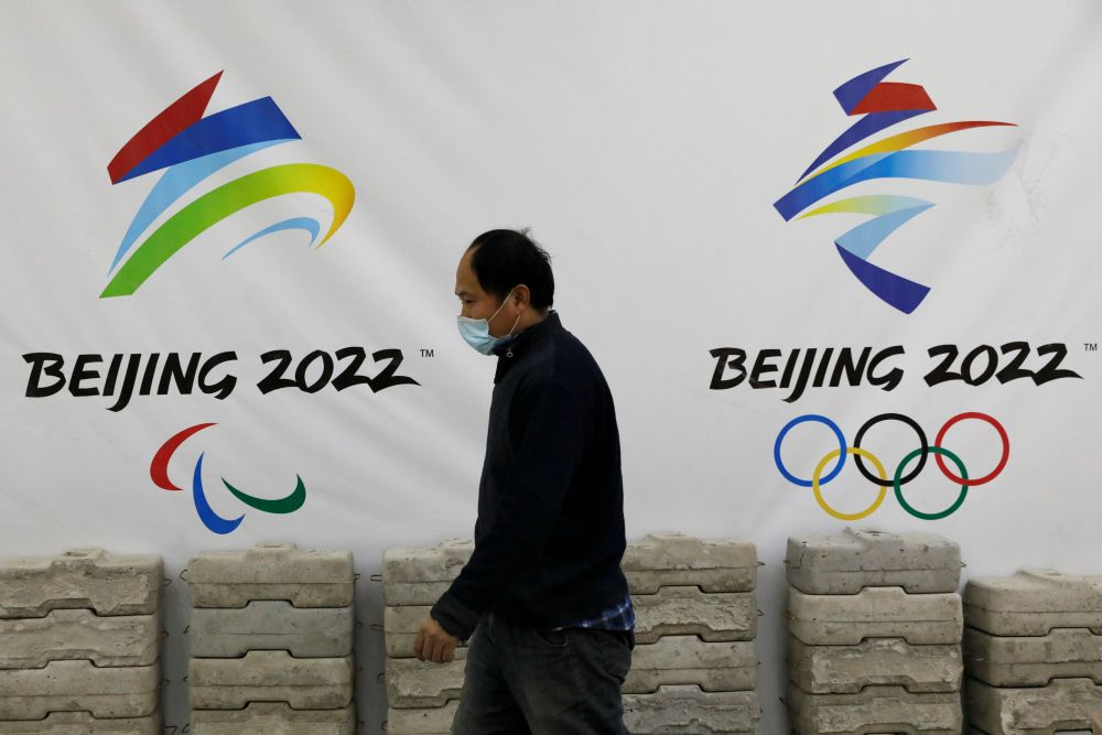 A man walks past a board with logos of 2022 Winter Olympic Games, at a souvenir shop under renovation in Beijing January 29, 2021. — Reuters pic