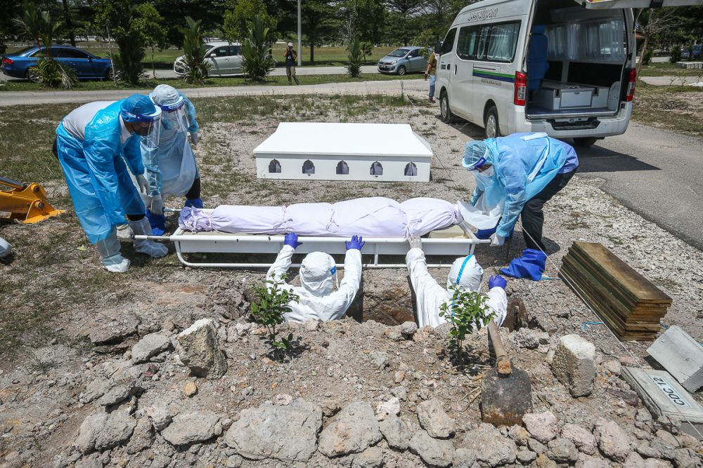 Workers wearing personal protective equipment bury the body of a Covid-19 victim at a cemetery in Shah Alam February 25, 2021. — File picture by Yusof Mat Isa