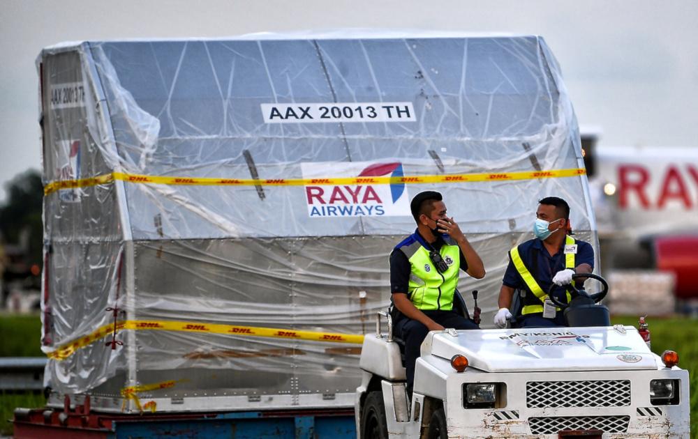 Staff of Raya Airways with the first batch of the Pfizer-BioNTech vaccine for Sarawak at the Kuching International Airport, February 24, 2021. — Bernama pic