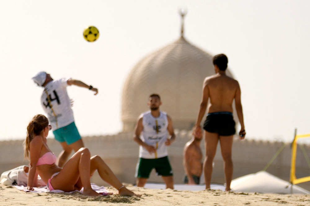 In this file photo taken July 24, 2020, a sunbather watches as people play during a beach volleyball tournament in the Gulf emirate of Dubai. — AFP pic