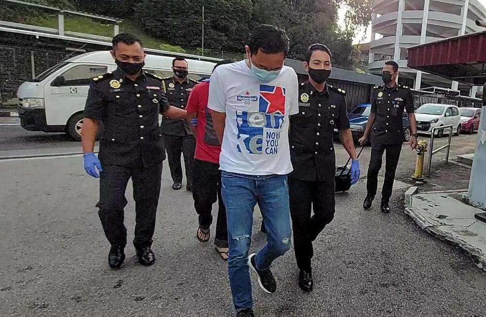 The company and two accused, as well as one who is still at large, are charged with using, possessing and offering 3,418 boxes of frozen food using false trade descriptions without approval at the Sessions Court in Johor Baru February 9, 2021. — Picture by Ben Tan