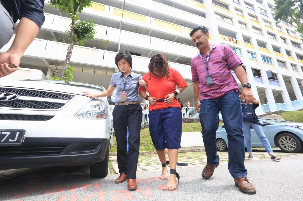 Gaiyathiri Murugayan being escorted by investigators to her Bishan flat in August 2016. — TODAY pic