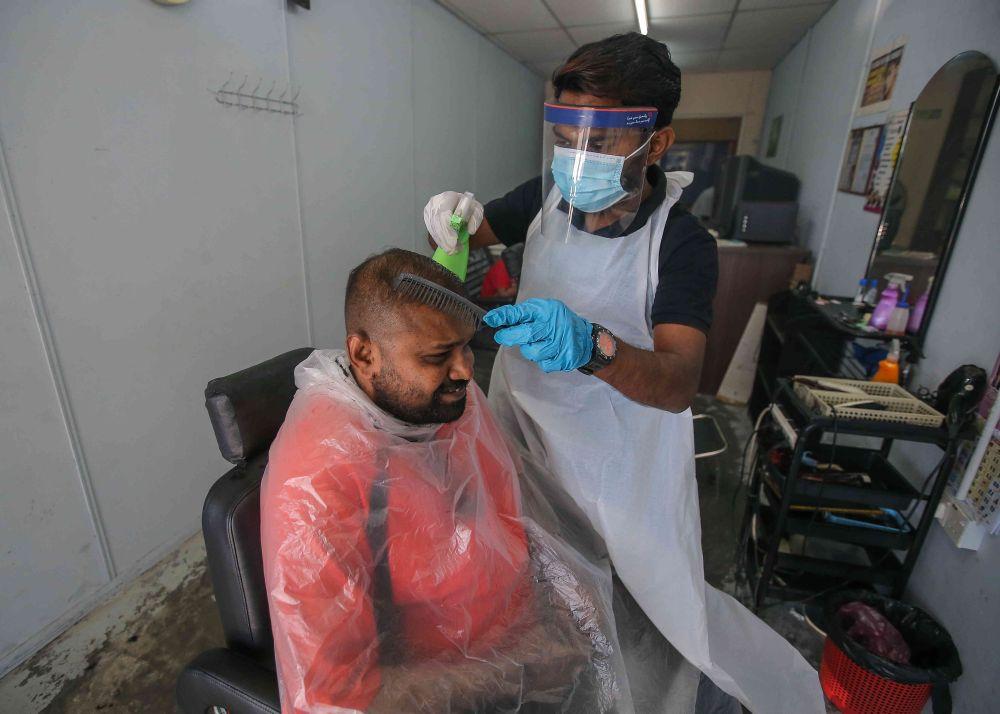 Barber Logasvaran Konasegaran gives his customer a haircut at his shop in Taman Tinggi, Ipoh February 5, 2021.  — Picture by Farhan Najib
