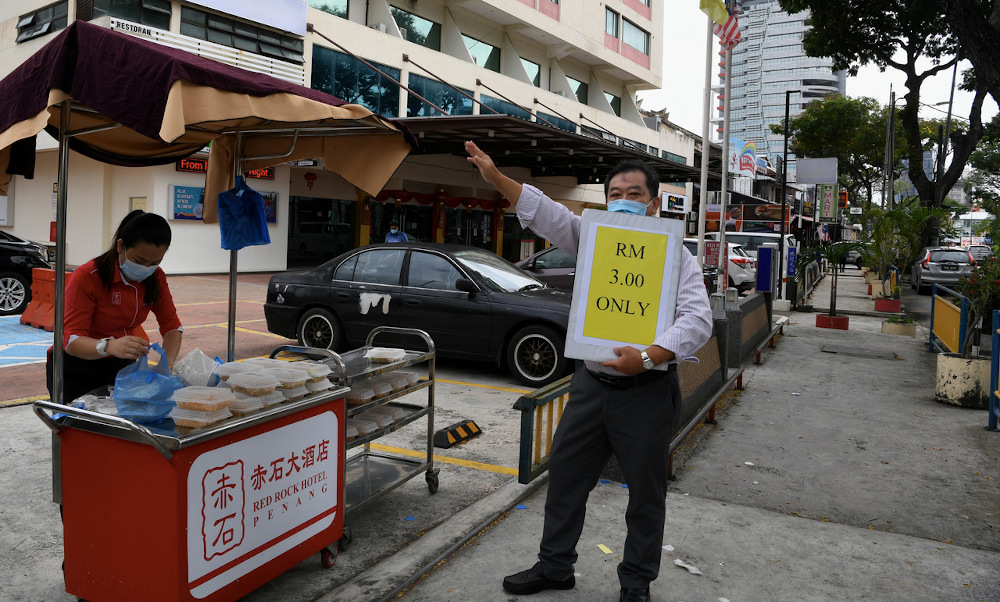 Jeffrey Lim (right) waving down customers to buy from the hotel's roadside food stall. — Bernama pic