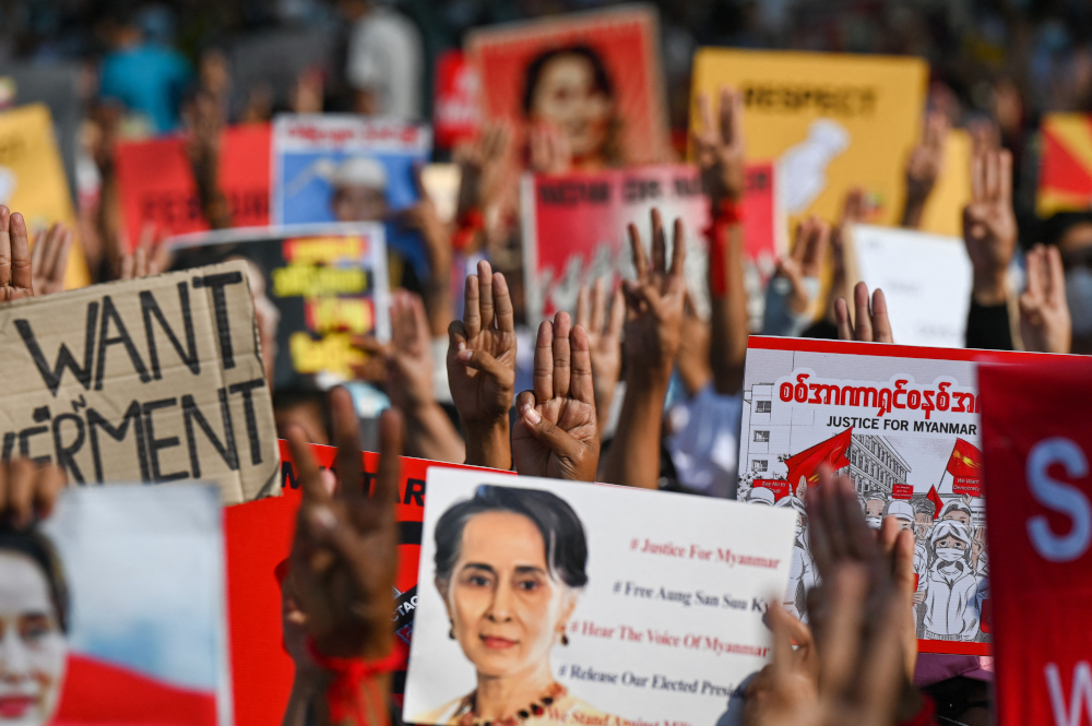 Protesters hold up the three finger salute with signs calling for the release of detained Myanmar civilian leader Aung San Suu Kyi during a demonstration against the military coup in Yangon February 16, 2021. — AFP pic