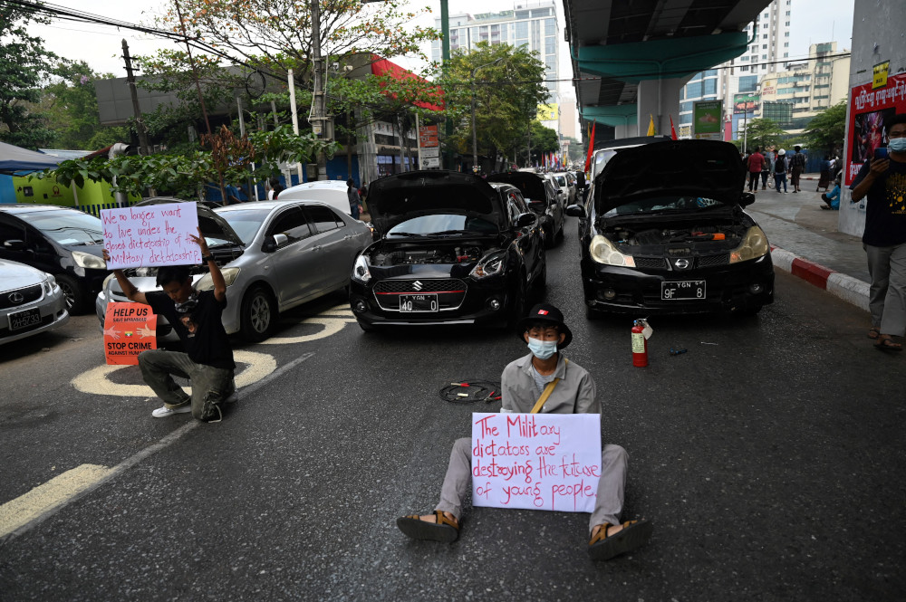 Protesters take part in a demonstration blocking a road with their cars and demanding the release of Aung San Suu Kyi during a demonstration against the military coup in Yangon February 18, 2021. — AFP pic