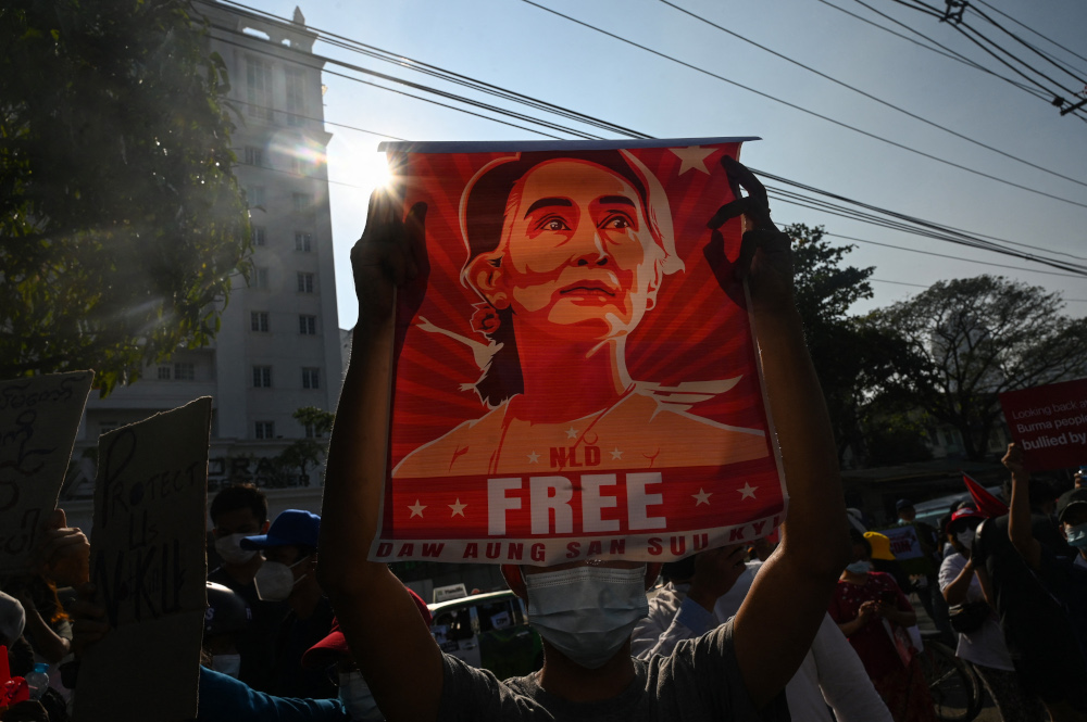 A protester holds up a poster featuring Aung San Suu Kyi during a demonstration against the military coup at in front of the Central Bank of Myanmar in Yangon February 15, 2021. — AFP pic