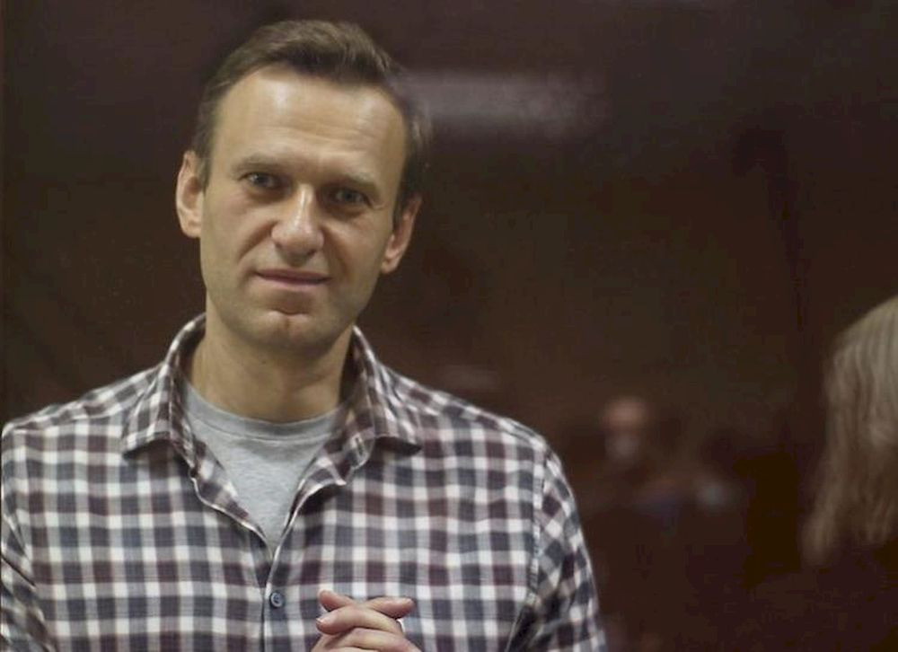 Kremlin critic Alexei Navalny, who is accused of slandering a Russian World War Two veteran, stands inside a defendant dock during a court hearing in Moscow, February 20, 2021, in this still image taken from video. — Babushkinsky District Court of Moscow/Handout via Reuters