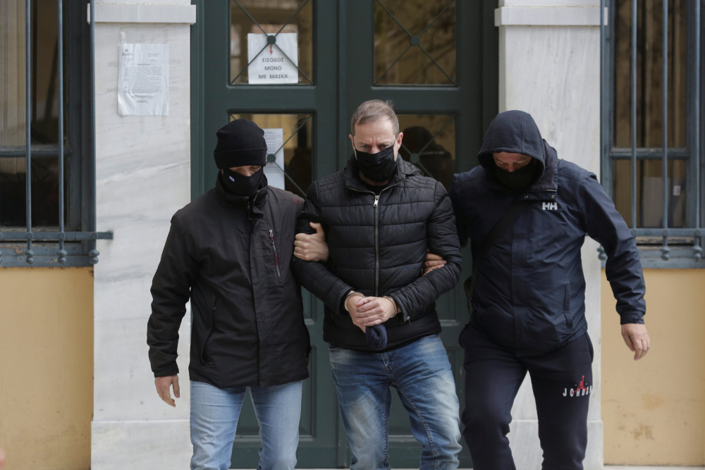 Greek actor and former director of Greece's National Theatre Dimitris Lignadis is escorted by plain clothes police officers as he leaves the prosecutor's office, in Athens February 21, 2021. — Reuters pic