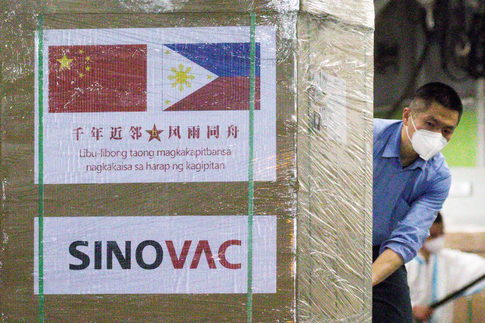 A worker unloads a box of Sinovac Biotech's CoronaVac Covid-19 vaccines from a Chinese military aircraft at Villamor Air Base in Pasay, Metro Manila February 28, 2021. — Reuters pic