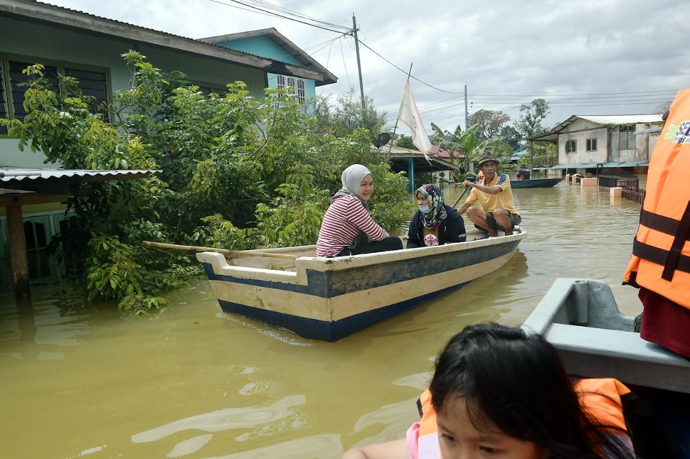 Villagers in Kampung Hulu Serian navigate through floodwater in Serian, Sarawak, February 5, 2021. — Bernama pic