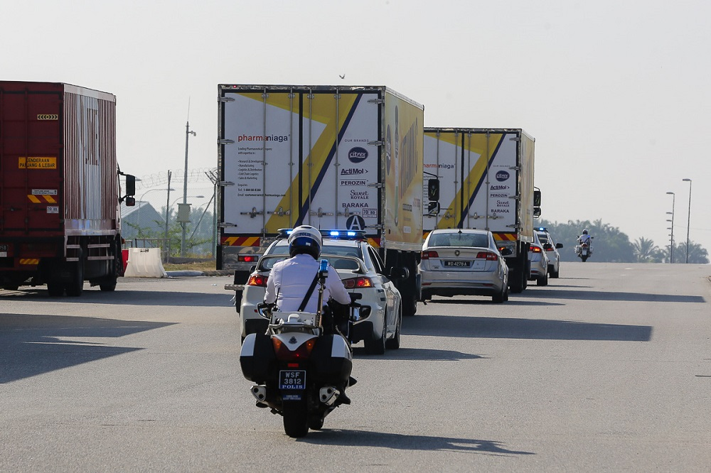 A convoy of vehicles carry the Sinovac Covid-19 vaccine with police escort from Cargo Village in KLIA February 27, 2021.