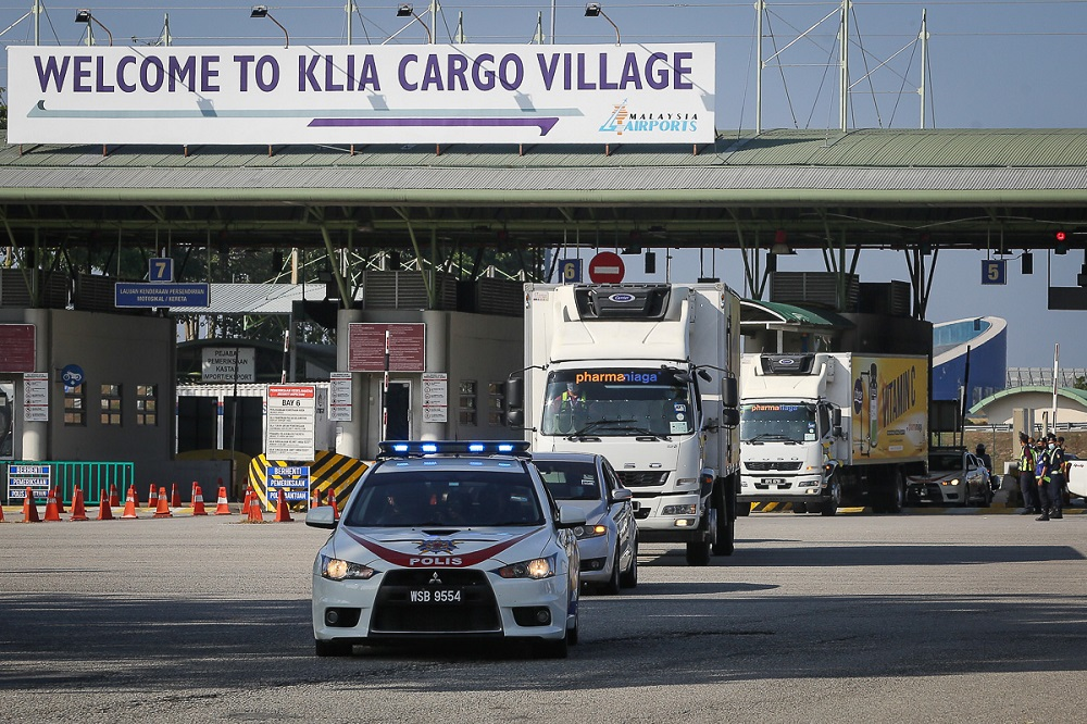 A convoy of vehicles carry the Sinovac Covid-19 vaccine with police escort from Cargo Village in KLIA February 27, 2021. ― Picture by Yusof Mat Isa