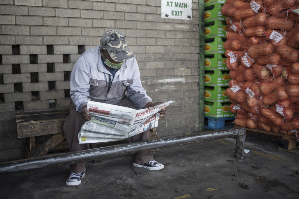 A man reads a newspaper next to a pallet of butternuts at the City Deep Fresh Product Market in Johannesburg, February 15, 2021. — AFP pic