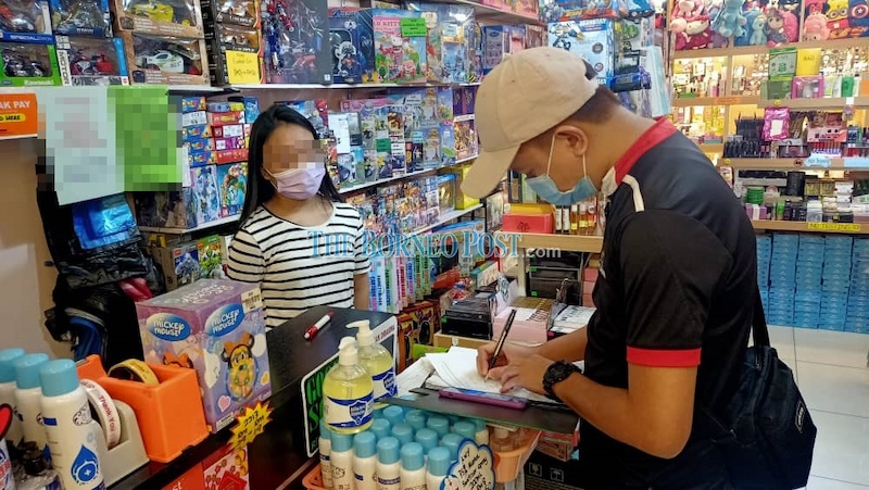A member of the inspection team member taking down details of a business premises during the operation. — Borneo Post Online