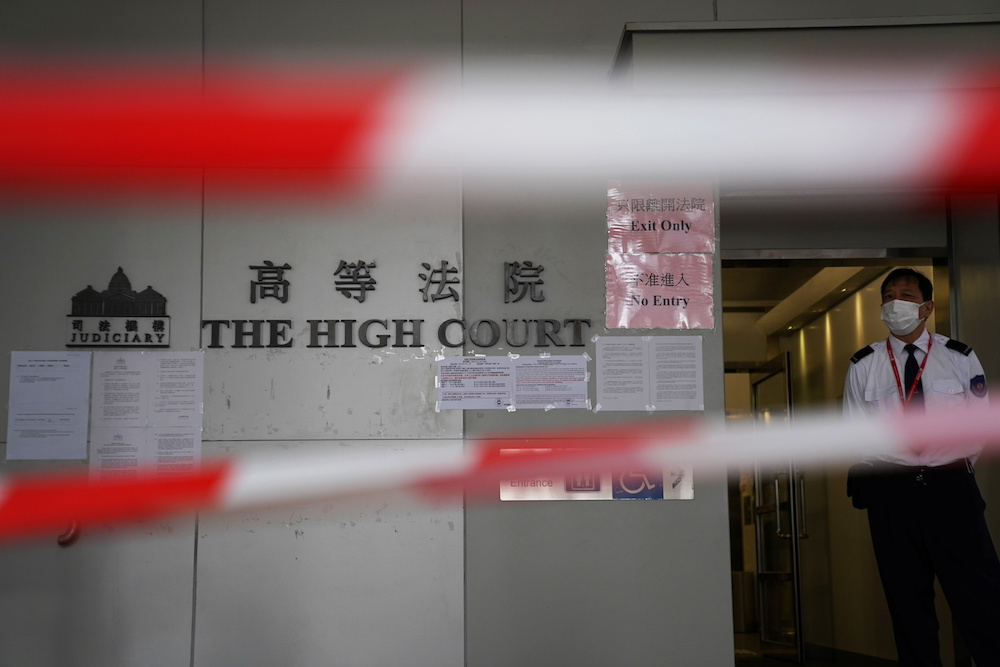 File photo of a guard standing behind cordons before a court hearing on the appeal against the bail release of 11 pro-democracy activists charged with national security violations, at the High Court in Hong Kong March 11, 2021. — Reuters pic