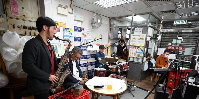 A jazz band live streaming their jazz performance in a noodle bar in Hong Kong. — AFP pic
