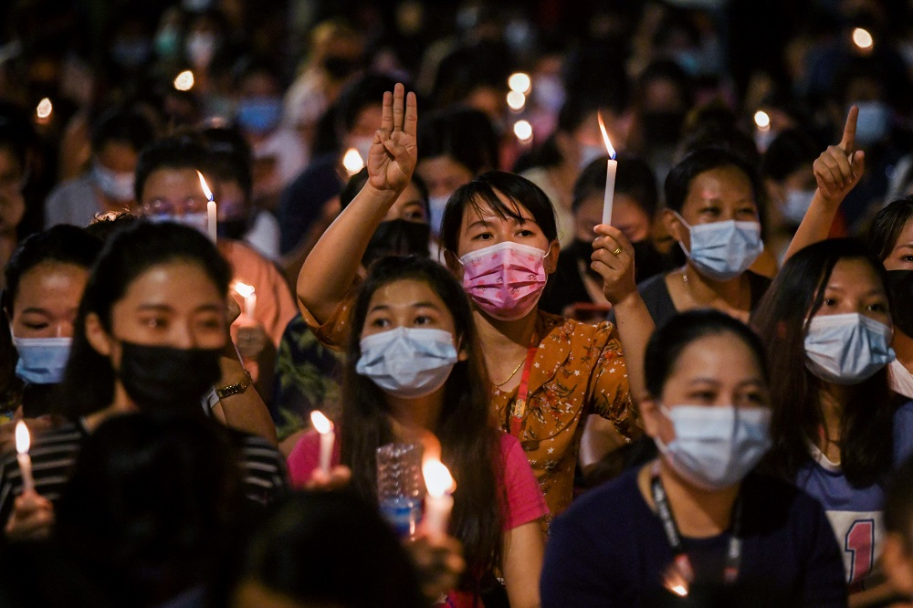 People hold candles as they take part in an anti-coup night protest at Hledan junction in Yangon March 14, 2021. — Reuters