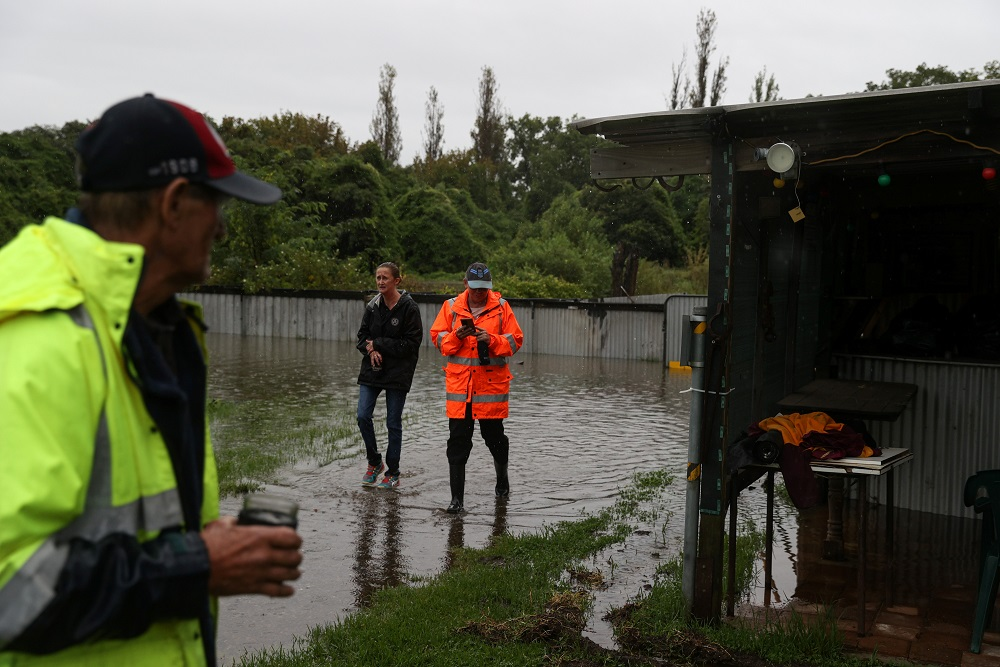Local residents walk through their property to check on a house while floodwaters rise in the suburb of Riverstone in Sydney March 22, 2021. — Reuters pic