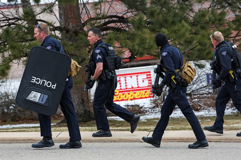Law enforcement officers sweep the parking lot at the site of a shooting at a King Soopers grocery store in Boulder, Colorado March 22, 2021. — Reuters pic