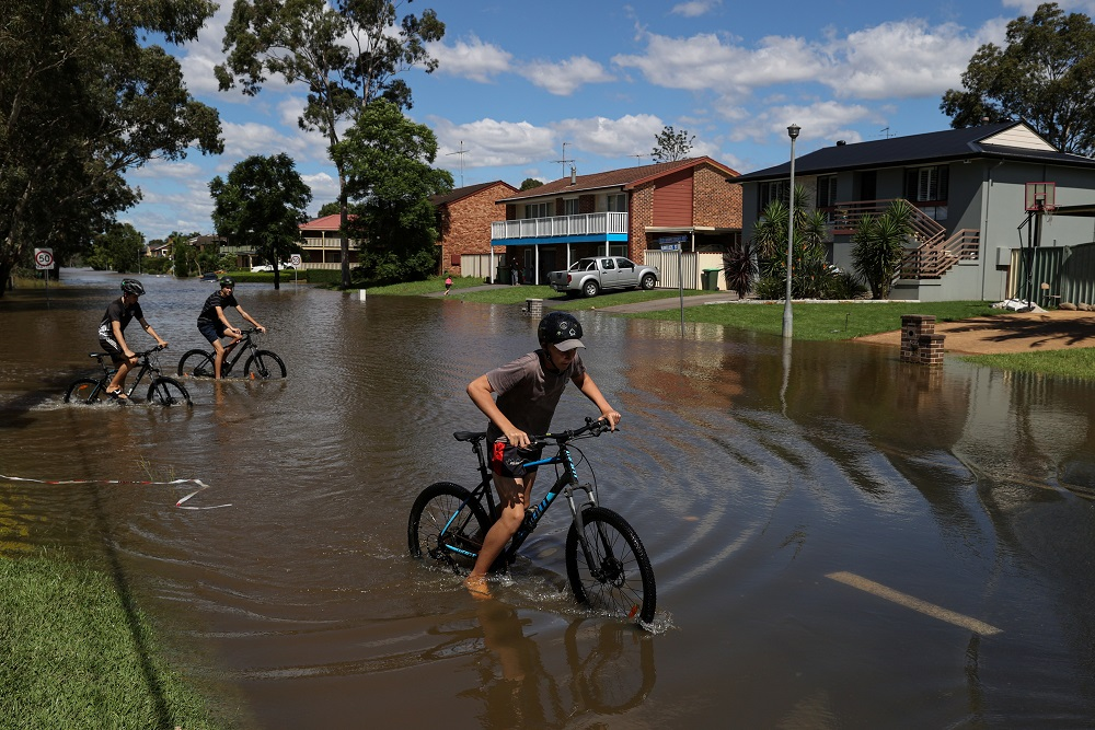 Kids ride bicycles through floodwaters as severe flooding affects the suburb of McGraths Hill after days of heavy rain in the state of New South Wales, in Sydney March 24, 2021. — Reuters pic