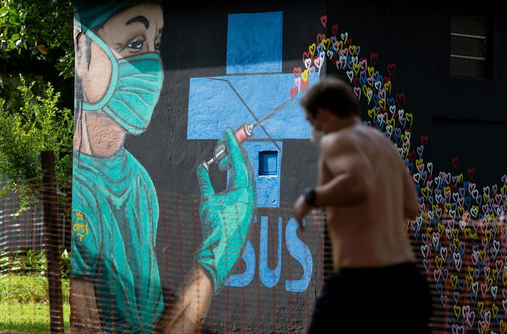 A man runs next to a graffiti near Gonzaga beach, after beaches in the coast of the state of Sao Paulo got closed as a restrictive measure to contain the outbreak of the coronavirus disease, in Santos, Sao Paulo state March 26, 2021. — Reuters pic
