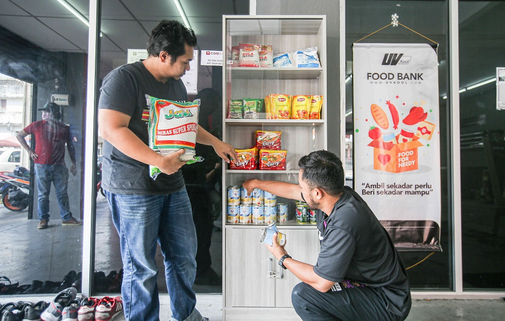 VKOOL: UV Kool Tint Ipoh operator Hafizee Arop (left) with his colleague Meor Safwan arrange items on the food bank that began operation on February 18, 2021. — Pictures by Farhan Najib