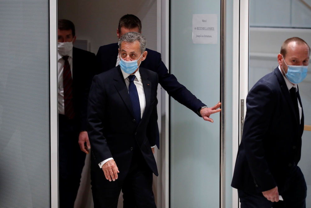 Former French President Nicolas Sarkozy, wearing a protective face mask, leaves after the verdict in his trial on charges of corruption and influence peddling, at Paris courthouse, France, March 1, 2021. — Reuters pic