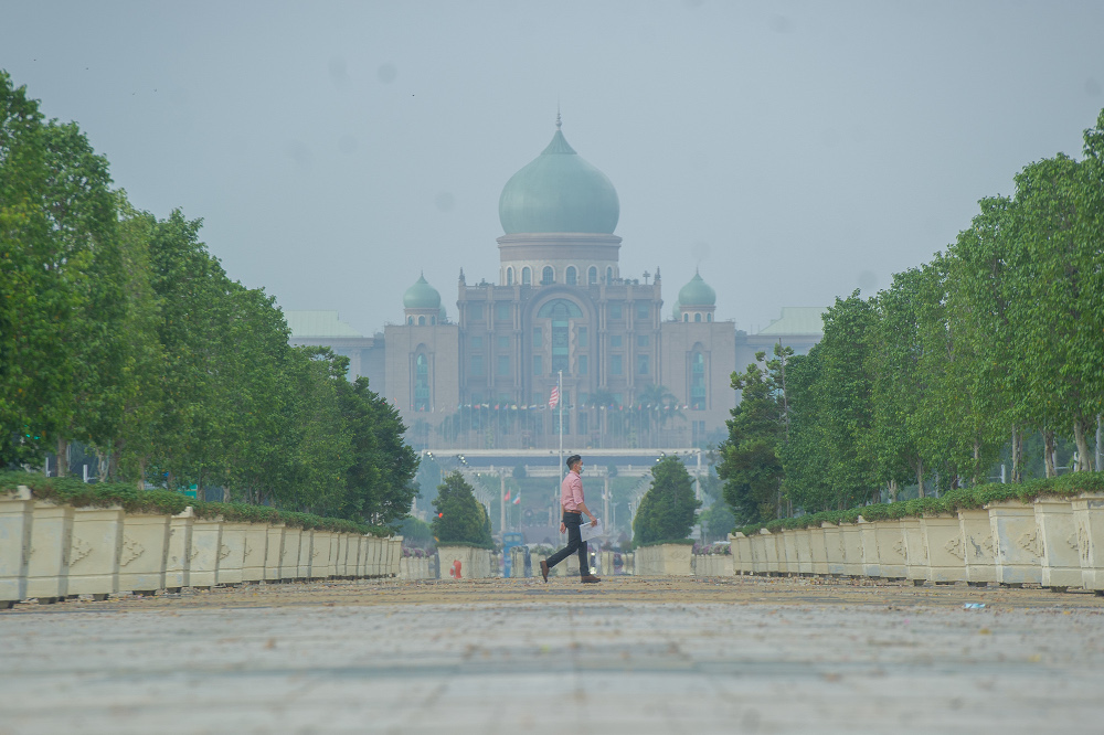 Pedestrians crossing the street against a hazy backdrop of the Perdana Putra building at Putrajaya Boulevard in Putrajaya March 2, 2021. — Picture by Shafwan Zaidon