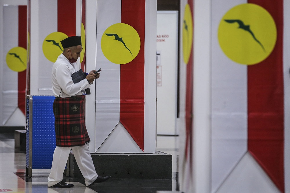 An Umno member arrives for the 2021 Umno annual general assembly in Kuala Lumpur March 27, 2021. ― Picture by Hari Anggara